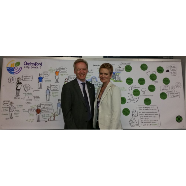 Stephen Robinson and Rose Moore in front of a visual record of the Chelmsford meeting that declared a cliimate emergency